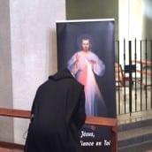 Un moine prie devant le tableau de Jésus Miséricordieux