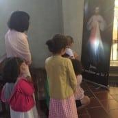 Une famille prie devant le tableau de Jésus Miséricordieux